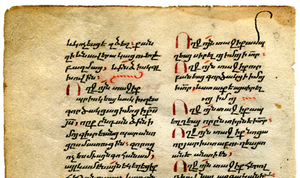The upper part of the verso of Leaf II shows the dirty, worn, and stained upper margin, the 2 columns of text in bolorgir minuscule script, enlarged initials in metallic red pigment (partly blackened through oxidation over time), section-ending markers in vegetal red pigment (still bright), and a distinctly elongated ascender for one letter in the top line.