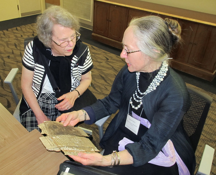 Two manuscript scholars confer about a manuscript fragment, brought to the event by request, at the 2015 Reception at the 50th International Congress on Medieval Studies. Photography by David Sorenson