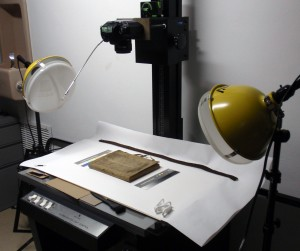 The Medieval-Psalter-Covered French Notebook in course of photography, archivally-sensitive equipment in place. Vire from the front cover, with untied ties. Photography © Mildred Budny. Reproduced by permission.