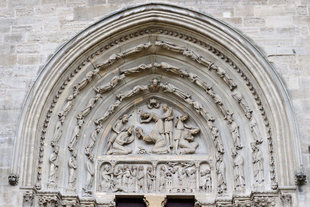 Architectural sculpture of the Tympanum and Archivolt of the North Transept Portal at the Basilica of Saint-Denis, including a representation of the decapitation of the saint. Photo Myrabella via Wikimedia Commons.