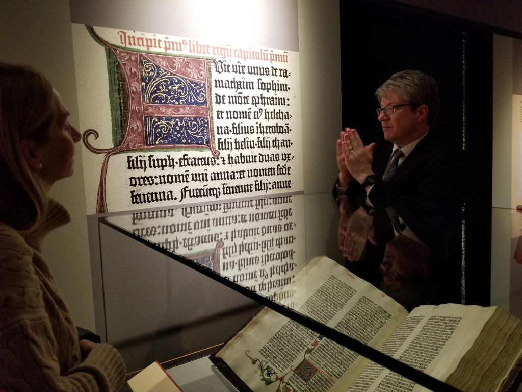 "At the Exhibition of ""Gutenberg and After"" at Princeton University in 2019, the Co-Curator Eric White stands before the Scheide Gutenberg Bible displayed at the opening of the Book of I Kings."